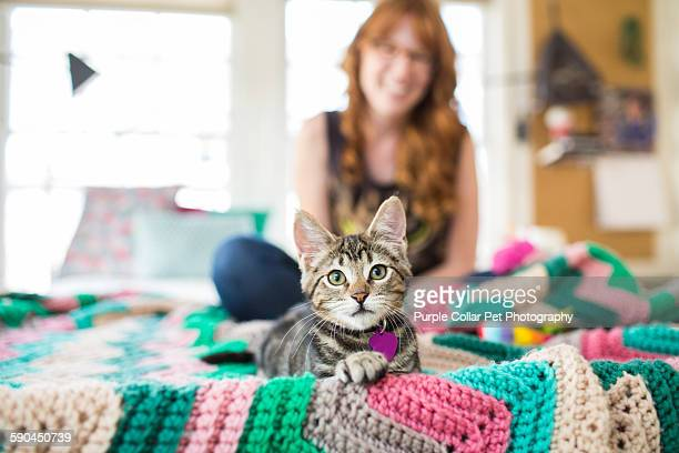 Kitten on bed with smiling young woman
