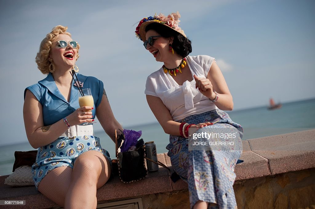 Kitty Steiner, 32 (L) and Jette Miranda, 29 dressed in fifties-style clothes talk during the 22th Rockin' Race Jamboree International Festival in Torremolinos on February 6 2016. AFP PHOTO/ JORGE GUERRERO / AFP / Jorge Guerrero