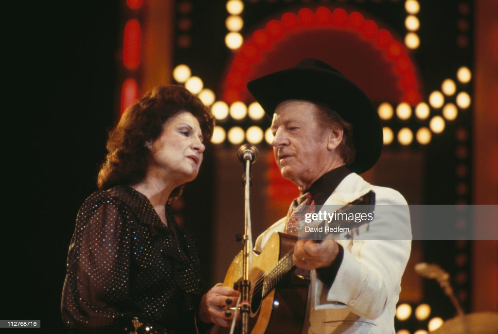 Kitty Wells, U.S. country singer, and her husband, country music singer Johnnie Wright, in concert, singing together with Wright playing a guitar, circa 1980.