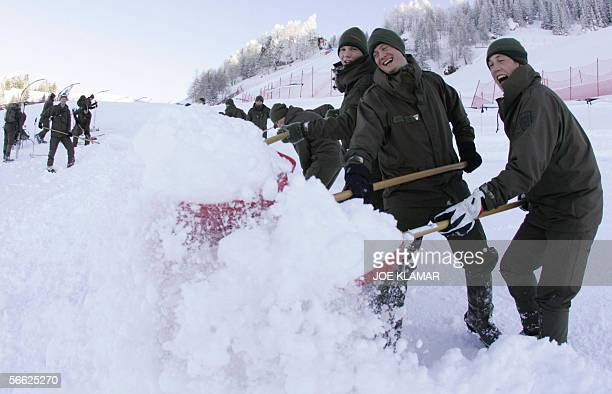 Austrian soldiers are on duty as they shovel off snow from the top part of the Kitzbuhel's men's World cup downhill course to prepare it for Friday's...