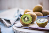 kiwi halves on wooden board, close up view,