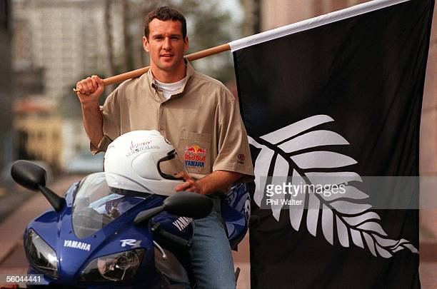Kiwi Motorcycling ace Simon Crafar holds a New Zealand silver fern flag attched to a rimu pole along with a 'Discover New Zealand' helmet presented...