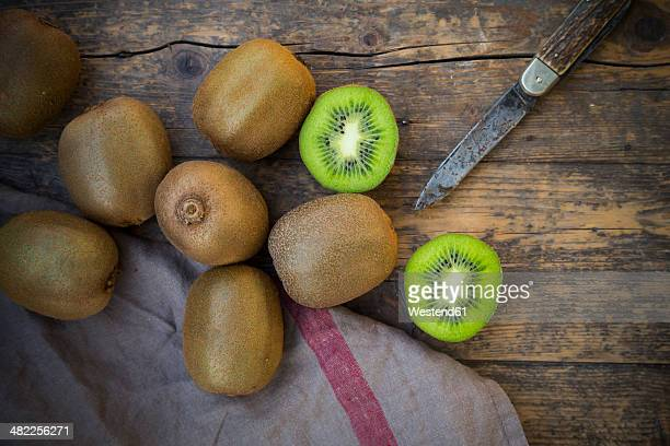 Kiwis (Actinidia deliciosa) and pocketknife on wooden table