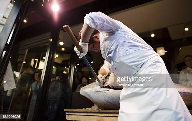 Kiyomura Co employee cuts a fresh bluefin tuna in front of one of the company's Sushi Zanmai sushi restaurants after the year's first auction at...