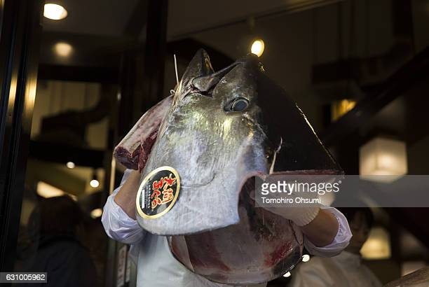Kiyomura Co employee holds the head of a fresh bluefin tuna in front of one of the company's Sushi Zanmai sushi restaurants after the year's first...