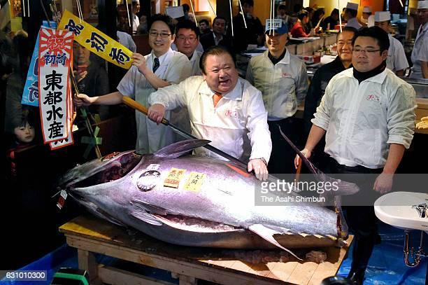 Kiyomura Co President Kiyoshi Kimura poses with a fresh bluefin tuna before cutting it in front of one of the company's Sushi Zanmai sushi...