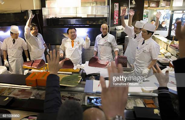 Kiyomura Co President Kiyoshi Kimura third from left gestures as he cuts portions of a fresh bluefin tuna inside one of the company's Sushi Zanmai...