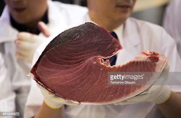 Kiyomura Co sushi chef holds a portion of a fresh bluefin tuna inside one of the company's Sushi Zanmai sushi restaurants after the year's first...