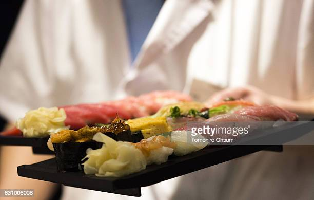 Kiyomura Co sushi chef serves a sushi plate inside one of the company's Sushi Zanmai sushi restaurants after the year's first auction at Tsukiji...