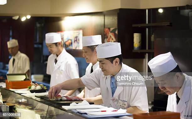 Kiyomura Co sushi chefs work inside one of the company's Sushi Zanmai sushi restaurants after the year's first auction at Tsukiji Market on January 5...
