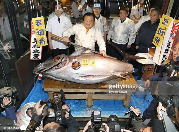 Kiyoshi Kimura president of Kiyomura Corp the operator of the Sushizanmai sushi restaurant chain poses on Jan 5 with the bluefin tuna he successfully...