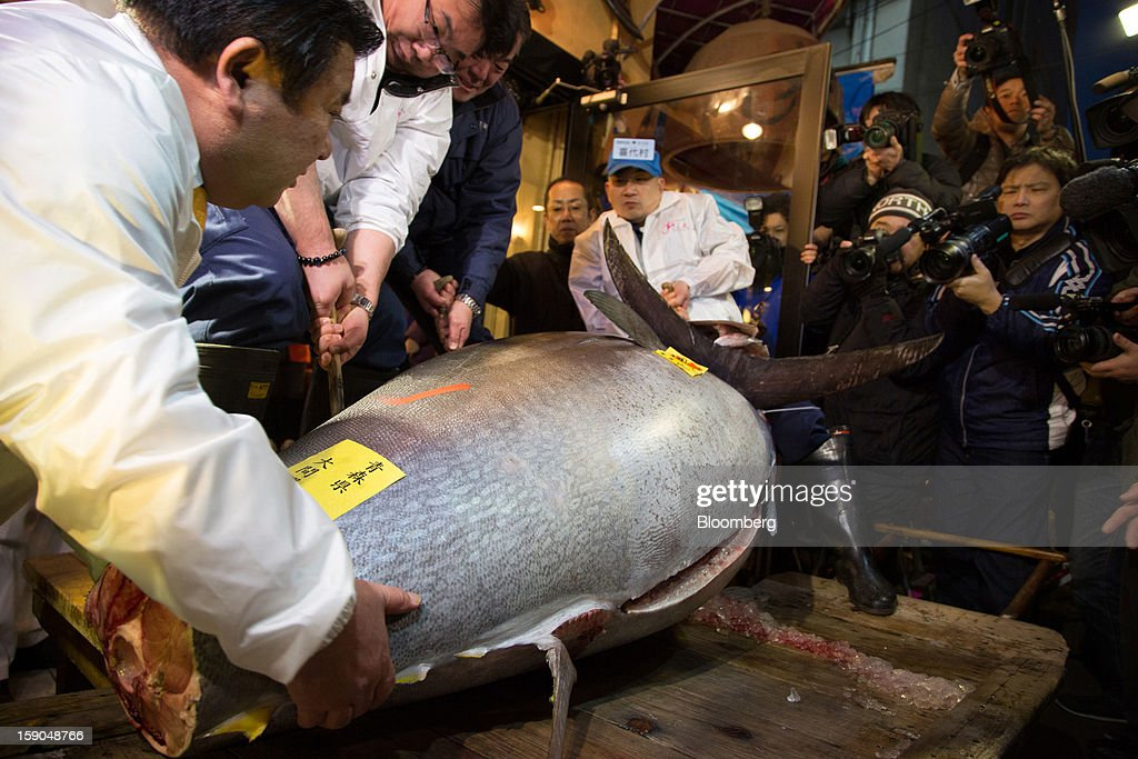 Kiyoshi Kimura, president of Kiyomura K.K., left, helps carry a 155.4 million yen ($1.76 million) fresh whole tuna weighing 222 kilograms (489 pounds), sold at the year's first auction at Tsukiji Market, in a Sushi Zanmai sushi restaurant in Tokyo, Japan, on Saturday, Jan. 5, 2013. Kiyomura, a Tokyo-based sushi chain operator, outbid rivals for a second year in a row for the most expensive fish ever sold at the market, saying the purchase may help improve Japan-China relations. Photographer: Noriyuki Aida/Bloomberg via Getty Images