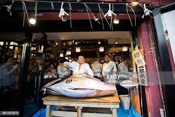 Kiyoshi Kimura president of sushi restaurant chain SushiZanmai poses with a 212kilogram bluefin tuna at his main restaurant near the Tsukiji fish...