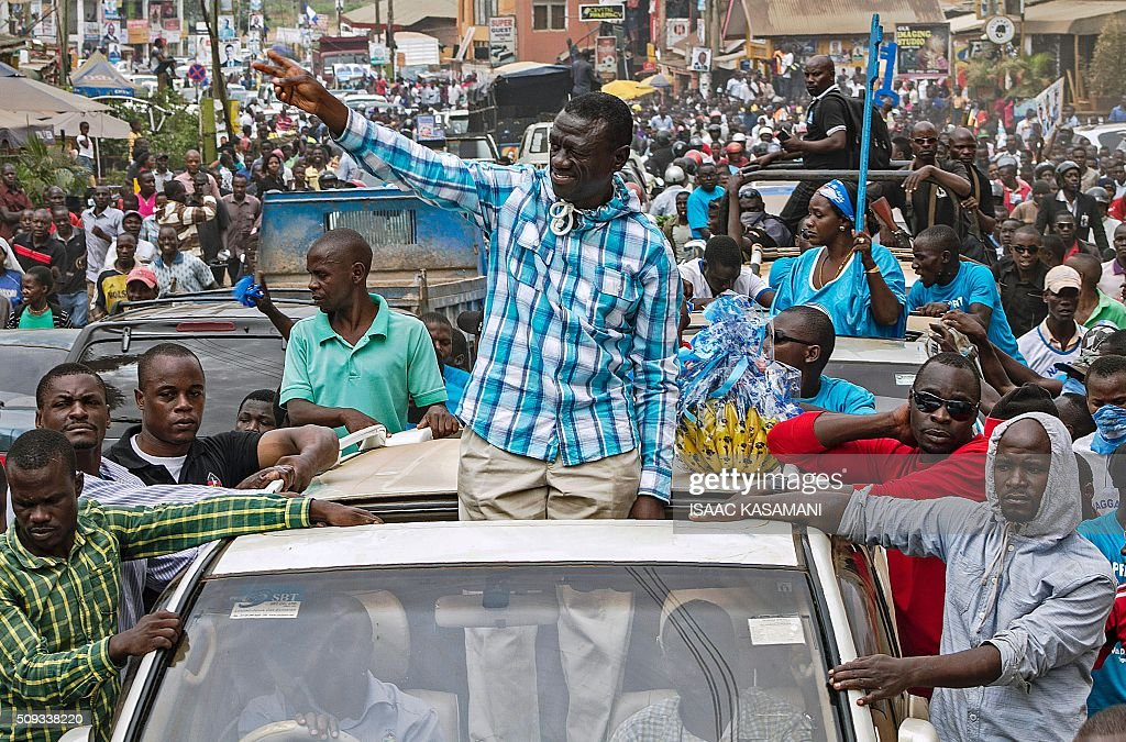 Kizza Besigye, Uganda's leading opposition leader and presidential candidate, stands outside the sunroof of a car and flashes the 'V for victory' sign to supporters during an election rally in Kampala on February 10, 2016. Besigye will challenge incumbent President Yoweri Museveni for the fourth time when voters go to the polls on February 18, 2016. / AFP / ISAAC KASAMANI