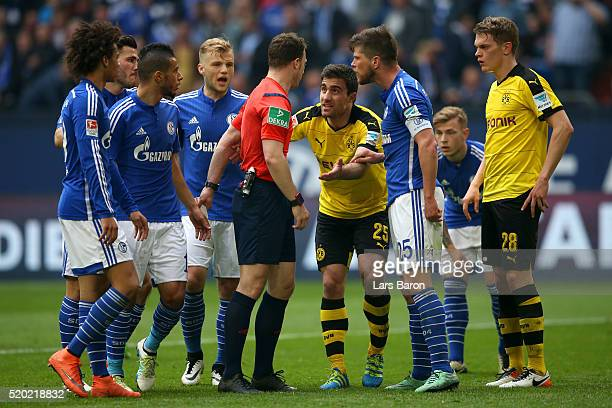 Klaas Jan Huntelaar of FC Schalke 04 and Sokratis Papastathopoulos of Borussia Dortmund speak with referee Felix Zwayer after he awarded a penalty to...