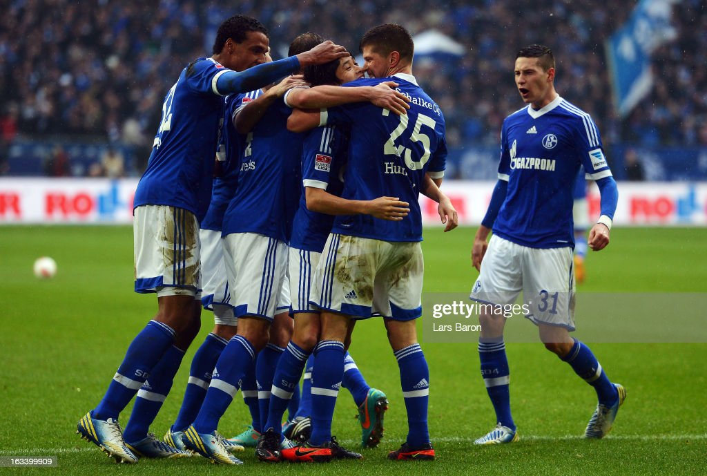 <a gi-track='captionPersonalityLinkClicked' href=/galleries/search?phrase=Klaas+Jan+Huntelaar&family=editorial&specificpeople=533040 ng-click='$event.stopPropagation()'>Klaas Jan Huntelaar</a> of Schalke celebrates with <a gi-track='captionPersonalityLinkClicked' href=/galleries/search?phrase=Atsuto+Uchida&family=editorial&specificpeople=4318608 ng-click='$event.stopPropagation()'>Atsuto Uchida</a> and other team mates after scoring his teams second goal during the Bundesliga match between FC Schalke 04 and Borussia Dortmund at Veltins-Arena on March 9, 2013 in Gelsenkirchen, Germany.