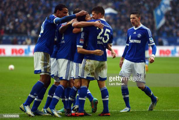 Klaas Jan Huntelaar of Schalke celebrates with Atsuto Uchida and other team mates after scoring his teams second goal during the Bundesliga match...