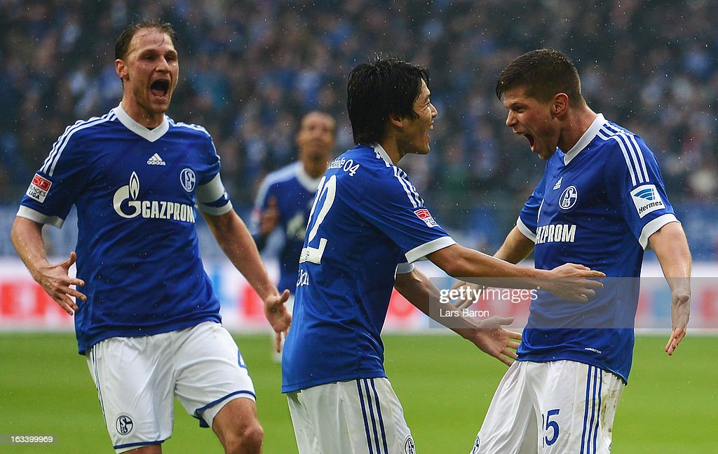 Klaas Jan Huntelaar of Schalke celebrates with Atsuto Uchida and other team mates after scoring his teams second goal during the Bundesliga match between FC Schalke 04 and Borussia Dortmund at Veltins-Arena on March 9, 2013 in Gelsenkirchen, Germany.