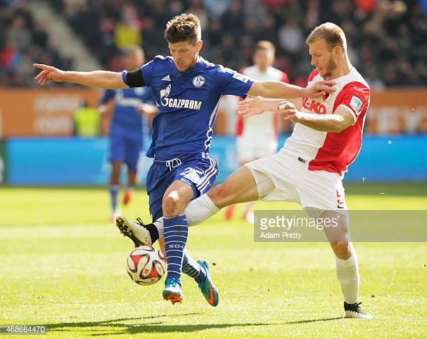 KlaasJan Huntelaar of FC Schalke is tackled by Ragnar Klavan of FC Augsburg during the Bundesliga match between FC Augsburg and FC Schalke 04 at SGL...