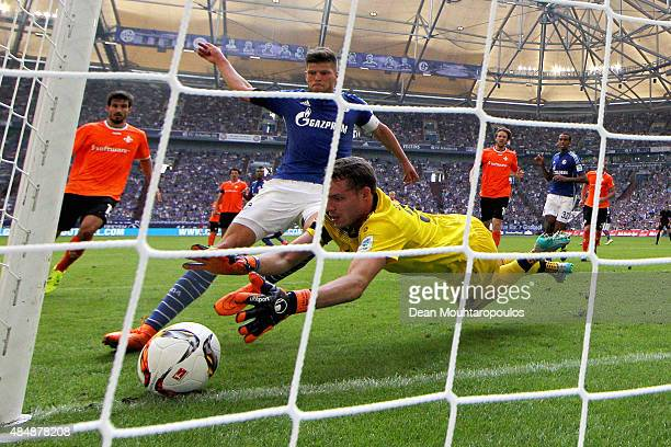 KlaasJan Huntelaar of Schalke battles for the ball with Goalkeeper Christian Mathenia of Darmstadt during the Bundesliga match between FC Schalke 04...