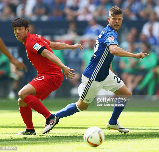 KlaasJan Huntelaar of Schalke battles for the ball with Hong Jeongho of FC Augsburg during the Bundesliga match between FC Schalke 04 and FC Augsburg...
