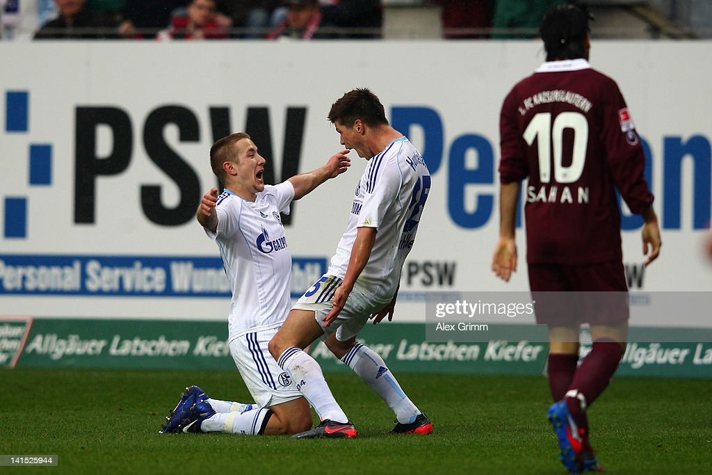 Klaas-Jan Huntelaar (C) of Schalke celebrates his team's second goal with team mate <a gi-track='captionPersonalityLinkClicked' href=/galleries/search?phrase=Lewis+Holtby&family=editorial&specificpeople=5351202 ng-click='$event.stopPropagation()'>Lewis Holtby</a> as Olcay Sahan of Kaiserslautern reacts during the Bundesliga match between 1. FC Kaiserslautern and FC Schalke 04 at Fritz-Walter-Stadion on March 18, 2012 in Kaiserslautern, Germany.