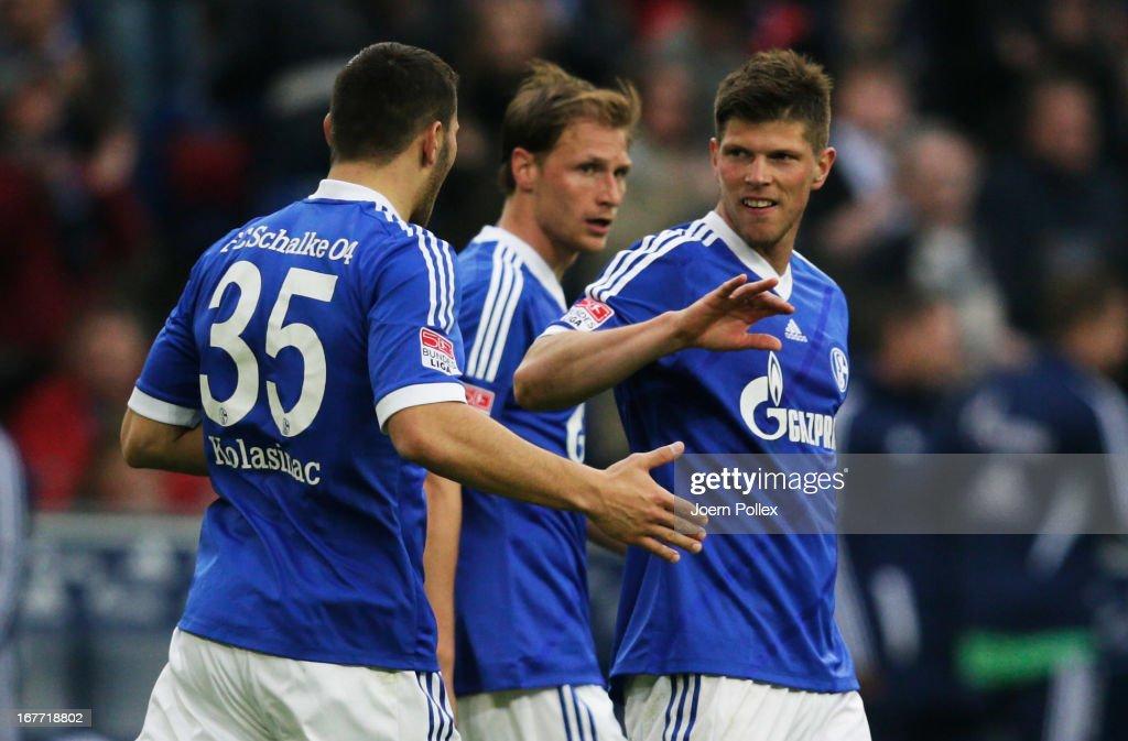 Klaas-Jan Huntelaar (R) of Schalke celebrates with his team mates after scoring his team's fourth goal during the Bundesliga match between FC Schalke 04 and Hamburger SV at Veltins-Arena on April 28, 2013 in Gelsenkirchen, Germany.