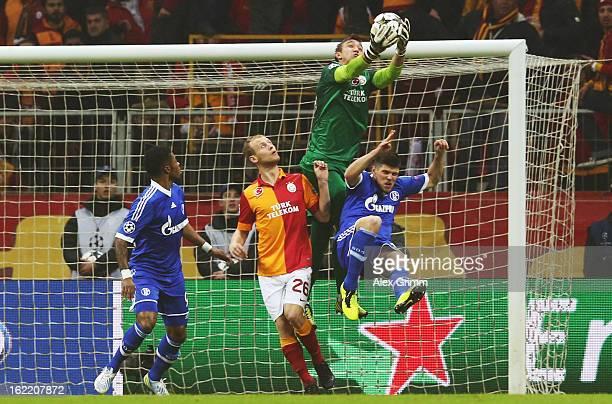 KlaasJan Huntelaar of Schalke is challenged by goalkeeper Fernando Muslera and Semih Kaya of Galatasaray during the UEFA Champions League Round of 16...