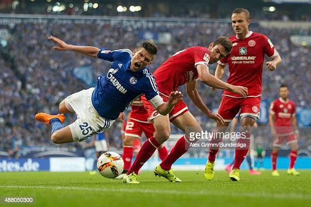 KlaasJan Huntelaar of Schalke is challenged by Stefan Bell and Pierre Bengtsson of Mainz during the Bundesliga match between FC Schalke 04 and 1 FSV...