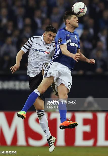 KlaasJan Huntelaar of Schalke jumps for a header with Achilleas Pouggouras of PAOK during the UEFA Europa League Round of 32 second leg match between...