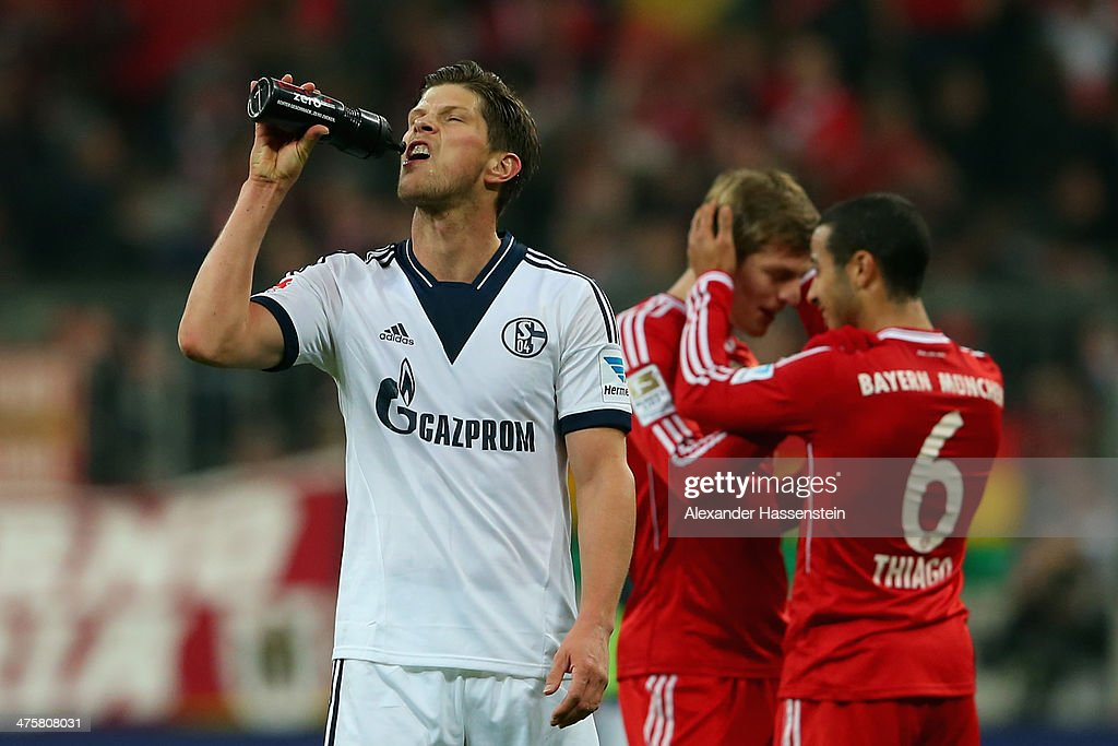 Klaas-Jan Huntelaar of Schalke reacts whilst Toni Kroos (2nd R) of Muenchen celebrates with his team mate Thiago after the Bundesliga match between FC Bayern Muenchen and FC Schalke 04 at Allianz Arena on March 1, 2014 in Munich, Germany.