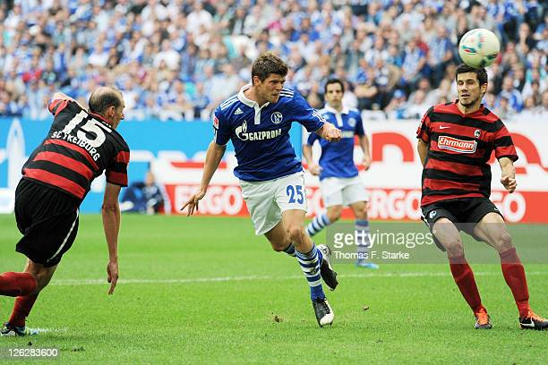 KlaasJan Huntelaar of Schalke scores his teams second goal against Oliver Barth and Mensur Mujdza of Freiburg during the Bundesliga match between FC...