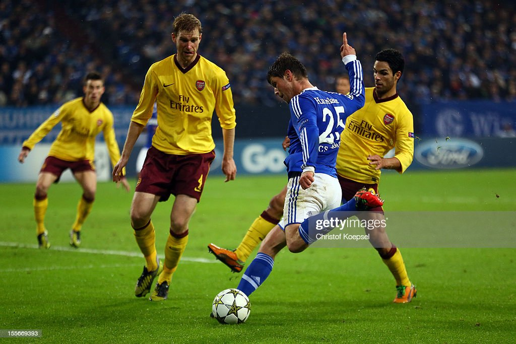 Klaas-Jan Huntelaar of Schalke (C) scores the first goal against <a gi-track='captionPersonalityLinkClicked' href=/galleries/search?phrase=Per+Mertesacker&family=editorial&specificpeople=207135 ng-click='$event.stopPropagation()'>Per Mertesacker</a> (L) and <a gi-track='captionPersonalityLinkClicked' href=/galleries/search?phrase=Mikel+Arteta&family=editorial&specificpeople=235322 ng-click='$event.stopPropagation()'>Mikel Arteta</a> of Arsenal (R) during the UEFA Champions League group B match between FC Schalke 04 and Arsenal FC at Veltins Arena on November 6, 2012 in Gelsenkirchen, Germany.