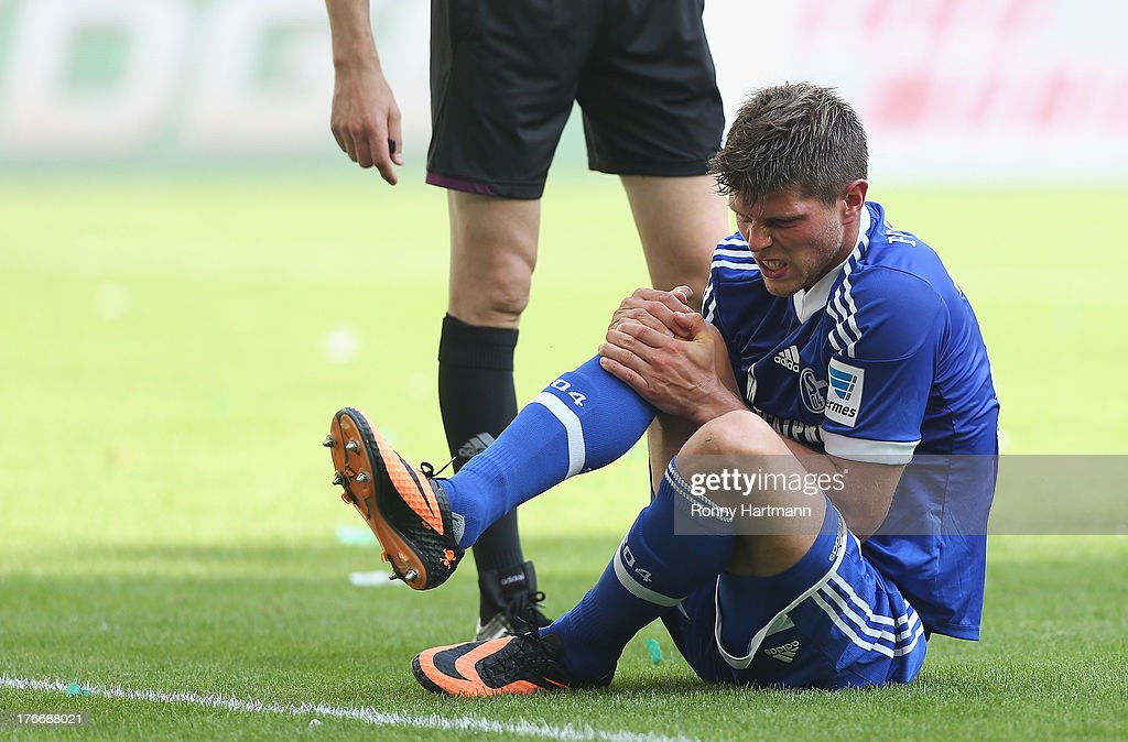 Klaas-Jan Huntelaar of Schalke sits on the pitch after suffering an injury during the Bundesliga match between VfL Wolfsburg and FC Schalke 04 at Volkswagen Arena on August 17, 2013 in Wolfsburg, Germany.