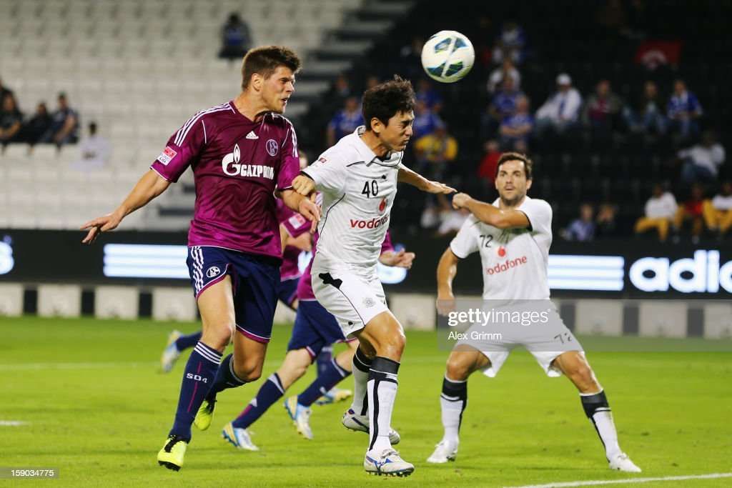 Klaas-Jan Huntelaar of Schalke tries to score against Jung Soo Lee of Al Sadd during the friendly match between Al-Sadd Sports Club and FC Schalke 04 at Jassim Bin Hamad Stadium on January 6, 2013 in Doha, Qatar.