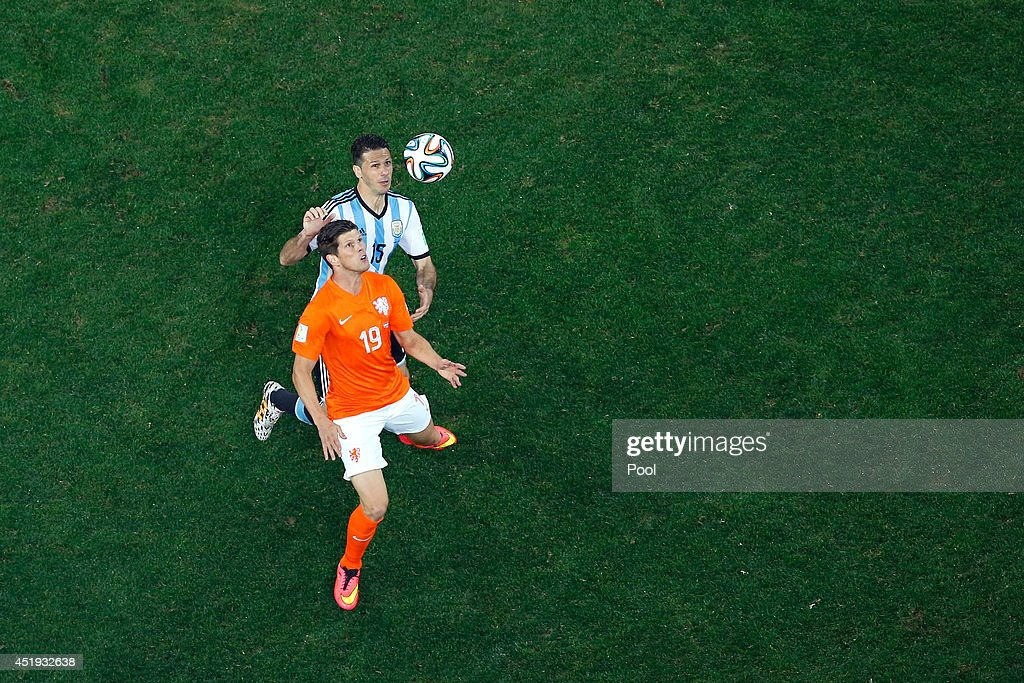 Klaas-Jan Huntelaar of the Netherlands controls the ball against Martin Demichelis of Argentina during the 2014 FIFA World Cup Brazil Semi Final match between the Netherlands and Argentina at Arena de Sao Paulo on July 9, 2014 in Sao Paulo, Brazil.