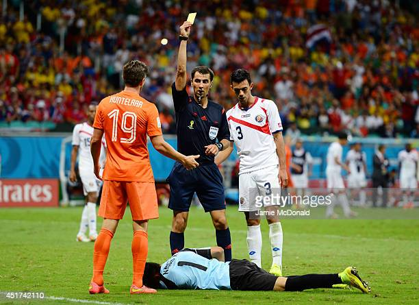 KlaasJan Huntelaar of the Netherlands is shown a yellow card by referee Ravshan Irmatov after a challenge on Keylor Navas of Costa Rica during the...