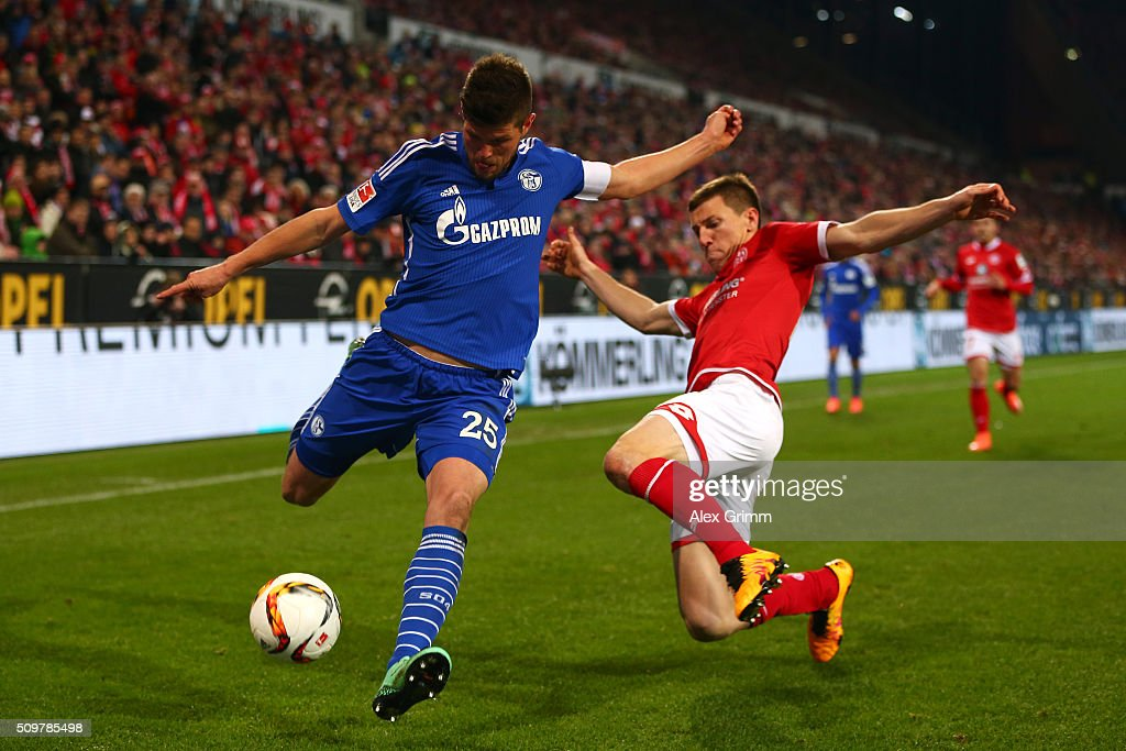 Klaas-Jan Hunterlaar of FC Schalke 04 battles for the ball with Gaetan Bussmann of 1. FSV Mainz 05 during the Bundesliga match between 1. FSV Mainz 05 and FC Schalke 04 at Coface Arena on February 12, 2016 in Mainz, Germany.