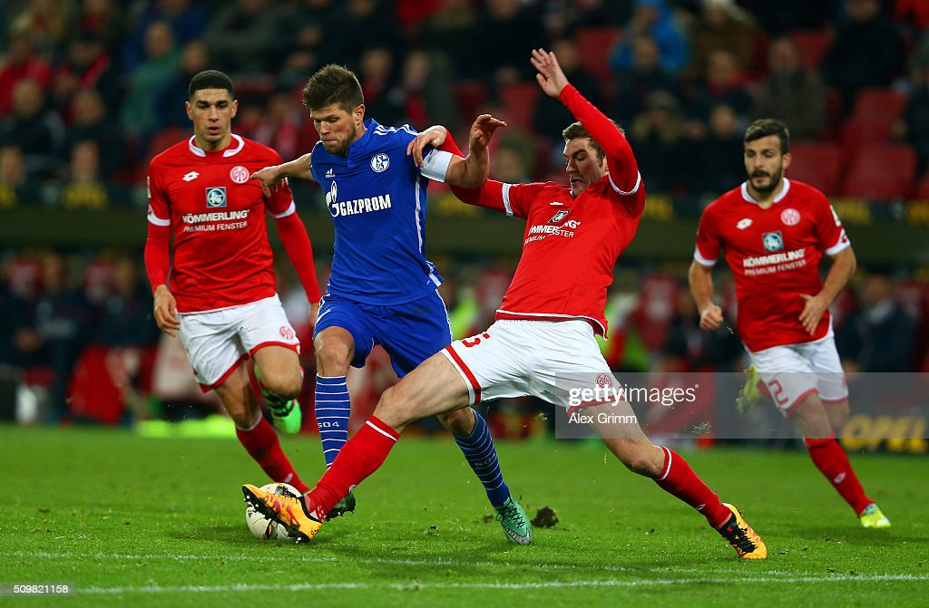 Klaas-Jan Hunterlaar of FC Schalke 04 battles for the ball with Stefan Bell of 1. FSV Mainz 05 during the Bundesliga match between 1. FSV Mainz 05 and FC Schalke 04 at Coface Arena on February 12, 2016 in Mainz, Germany.