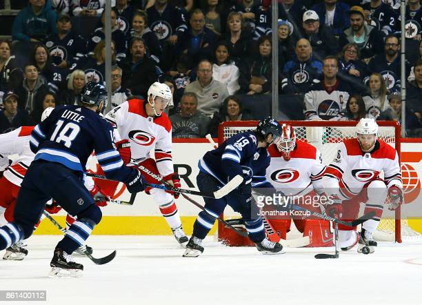 Klas Dahlbeck of the Carolina Hurricanes blocks the puck in front of goaltender Scott Darling as Nic Petan of the Winnipeg Jets looks on during first...