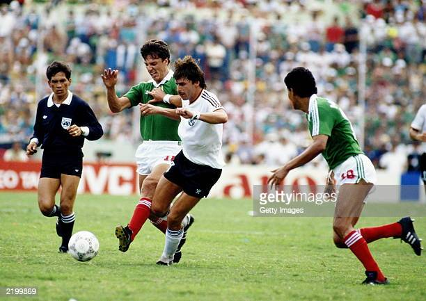 Klaus Allofs of West Germany is tackled by Rafael Amador of Mexico during the FIFA World Cup Finals 1986 Quarter Final match between West Germany and...