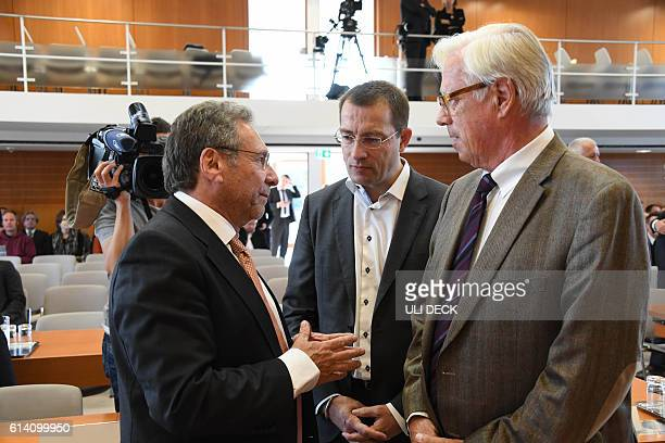 Klaus Ernst of the leftwing Die Linke party talks with appellants Roman Huber of the association 'More Democracy' and Thilo Bode chairman of...