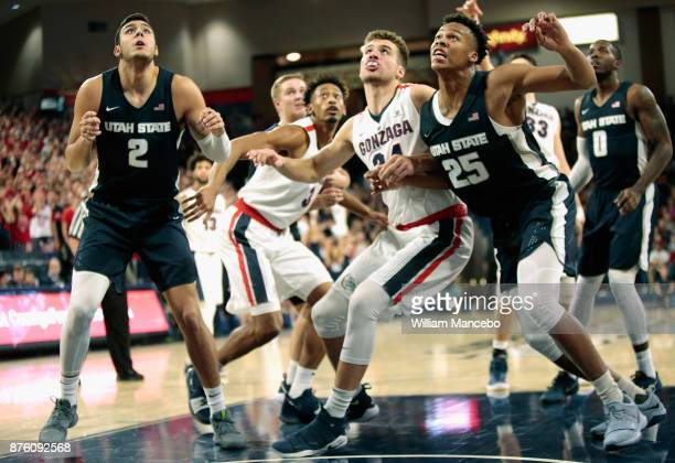 Klay Stall and Dwayne Brown Jr #25 of the Utah State Aggies look to rebound against Corey Kispert of the Gonzaga Bulldogs in the game at McCarthey...