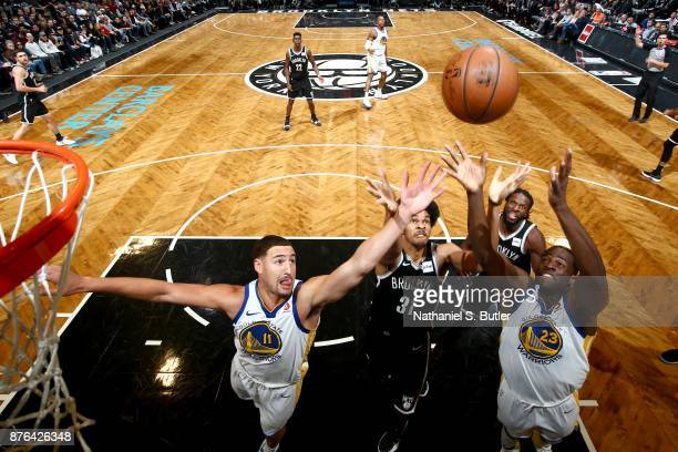 Klay Thompson and Draymond Green of the Golden State Warriors and Jarrett Allen of the Brooklyn Nets jump for the rebound on November 19 2017 at...