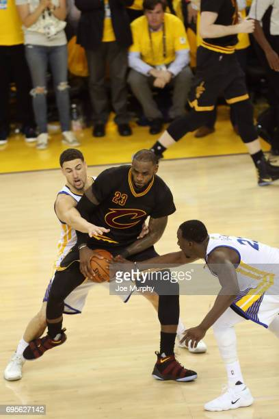 Klay Thompson and Draymond Green of the Golden State Warriors guard LeBron James of the Cleveland Cavaliers in Game Five of the 2017 NBA Finals on...
