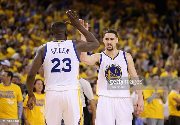 Klay Thompson and Draymond Green of the Golden State Warriors celebrate in the final minute of their victory over the Portland Trail Blazers in Game...