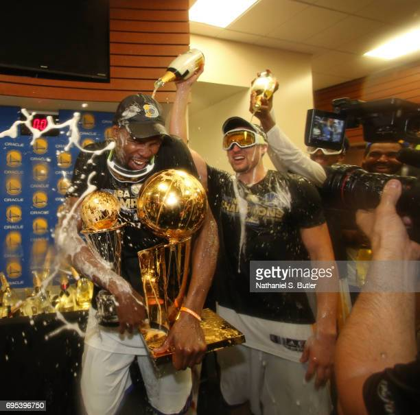Klay Thompson and Kevin Durant of the Golden State Warriors celebrates and holds the Larry O'Brien Trophy and the Bill Russell Finals MVP Trophy in...