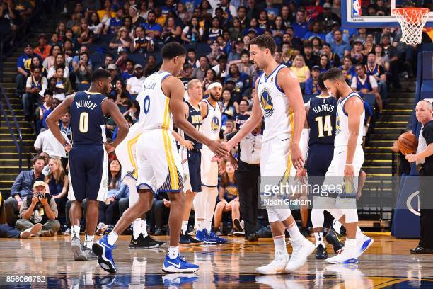 Klay Thompson and Patrick McCaw of the Golden State Warriors high five each other during the game against the Denver Nuggets during a preseason game...