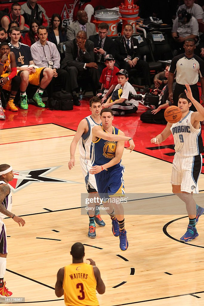 Klay Thompson #11 of Team Shaq passes against Alexey Shved #1 and Nikola Vucevic #9 of team Chuck during the 2013 BBVA Rising Stars Challenge on February 15, 2013 at the Toyota Center in Houston, Texas.