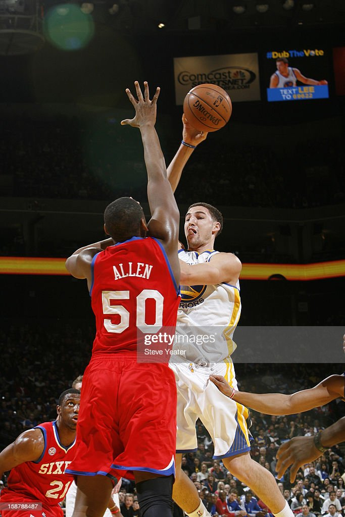 Klay Thompson #11 of the Golden State Warriors attempts a shot against Lavoy Allen #50 of the Philadelphia 76ers on December 28, 2012 at Oracle Arena in Oakland, California.
